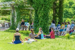 Students and adults meditating in Garden